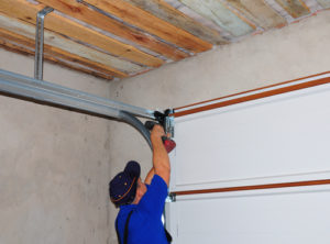 Contractor Installing Garage Door Post Rail and Spring